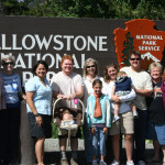 a family standing in front of the yellowstone sign