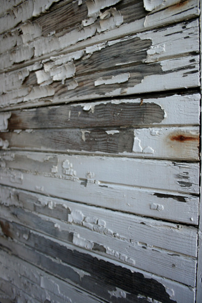 wooden wall with white paint that is mostly chipped off