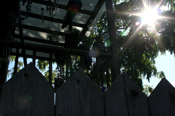 the top of a wooden fence with the sun shining through