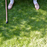 photograph of mostly grass with an old man's feet sticking out from the top