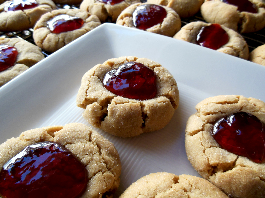 peanut butter and jelly cookies on a white plate with a few more in the background