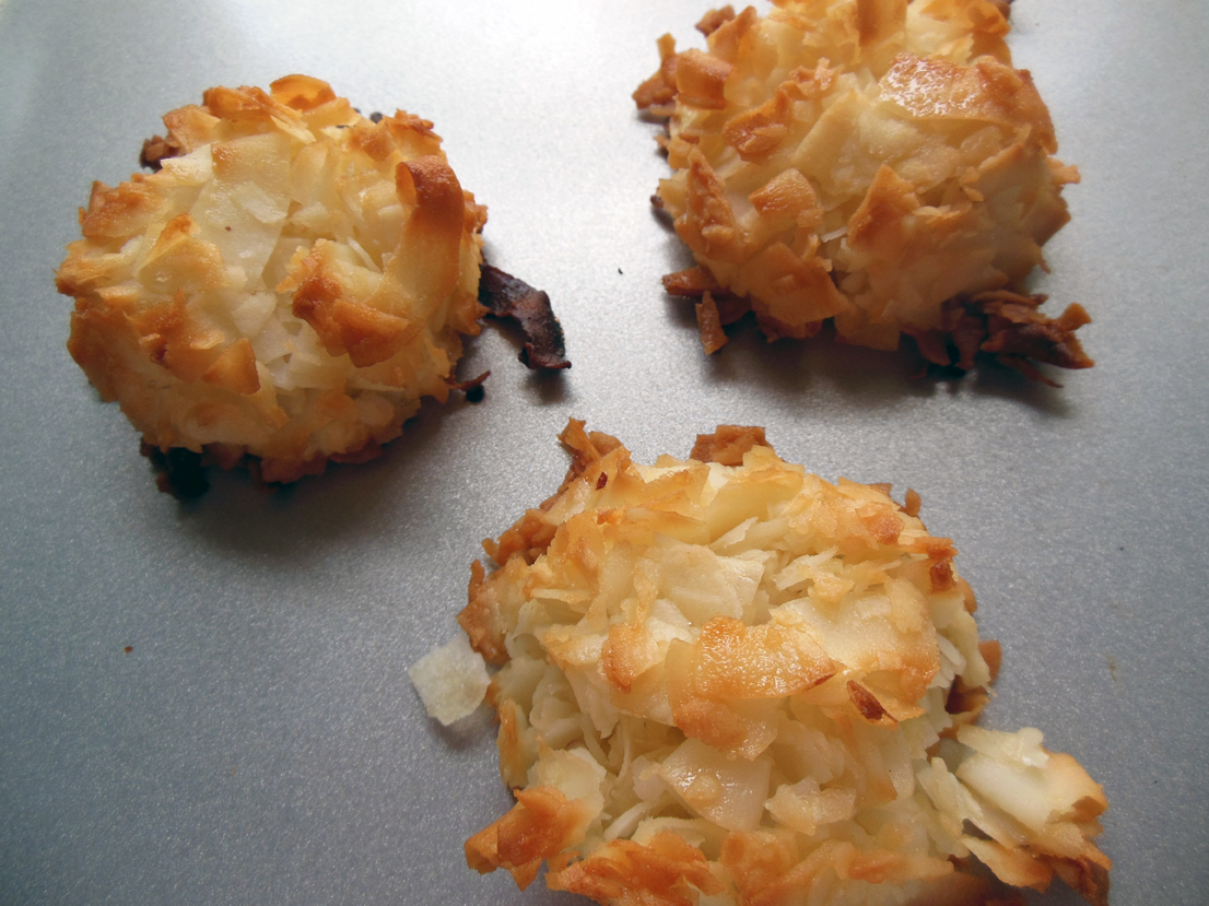 three coconut macaroons sit on a baking sheet