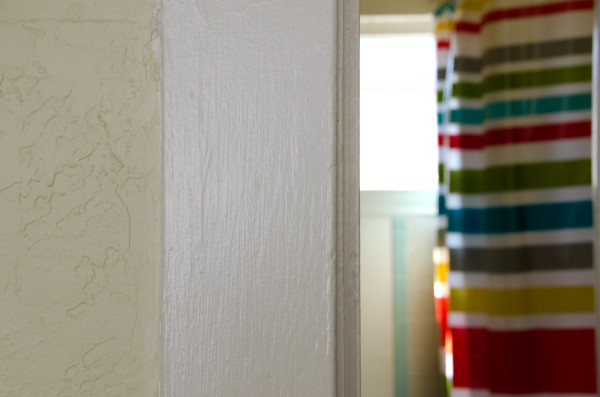 a wall with a striped bath curtain in the distance