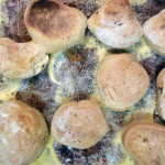A grid like photograph of english muffins sitting on a baking sheet